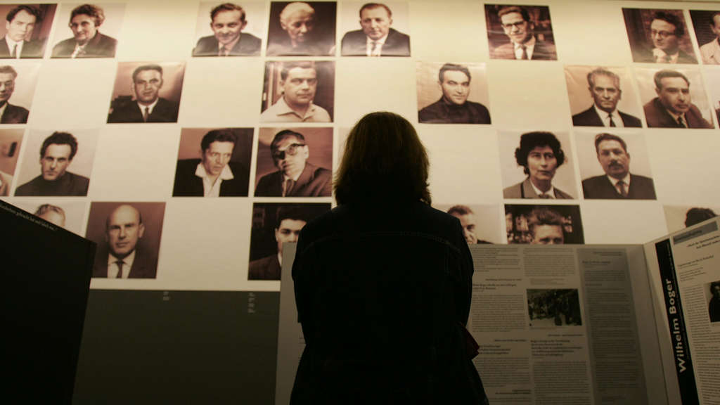 "(FILES) In this file photo taken on November 14, 2004, a visitor faces a wall of photographs depicting survivors of the Auschwitz concentration camp who testified in the so-called ""Frankfurt Trial"", at the Martin Gropius Museum in Berlin, including previously unreleased sound recordings detailing the proceedings during which Nazi camp commanders at Auschwitz were finally put on trial. The case files of the first Frankfurt Auschwitz Trial (1963 - 1965) officially were added to the Memory of the World register of the UNESCO on May 16, 2018. / AFP PHOTO / John MACDOUGALL"
