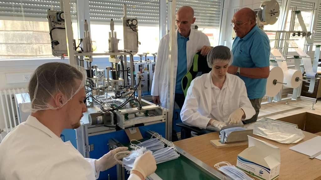 Tim Kerber, links, übergibt die Masken nach einer Qualitätskontrolle seinem Bruder Dennis, der dann jeweils 50 Masken verpackt. Vater Guido und Großvater Werner überwachen die Produktion.