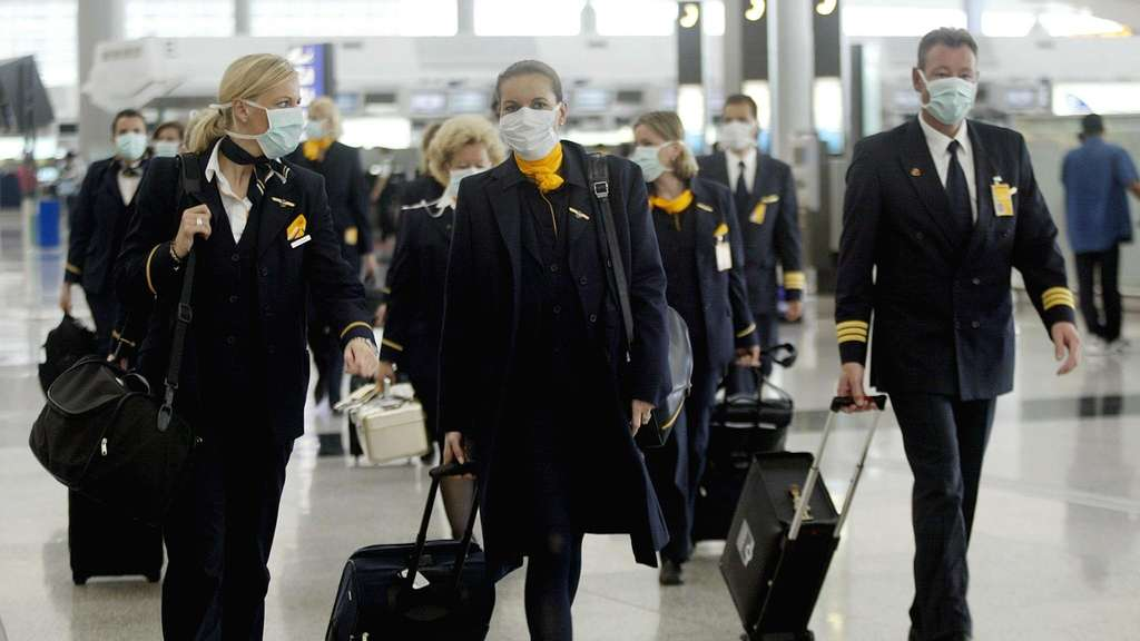 Aircrew for Germany's Lufthansa walk through Hong Kong's Chek Lap Kok wearing masks to protect against a killer outbreak of pneumonia 14 April 2003.